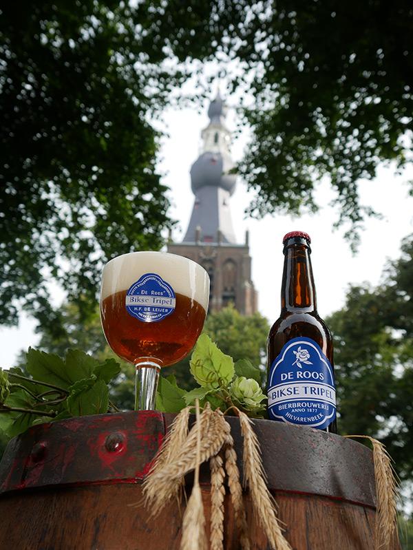 Een glas Bikse Tripel met de Bikse Toren op de achtergrond.